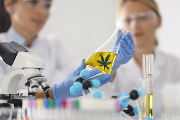 Kobiety w laboratorium chemicznym trzymają w ręku szklaną kolbę z olejem konopnym w zbliżenie niebieskie gumowe rękawiczki. rozwój laboratoriów medycznych do produkcji koncepcji środków odurzających.