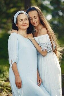 Kobiety w letnim lesie. pani w niebieskiej sukience. rodzina pozuje i obejmuje.