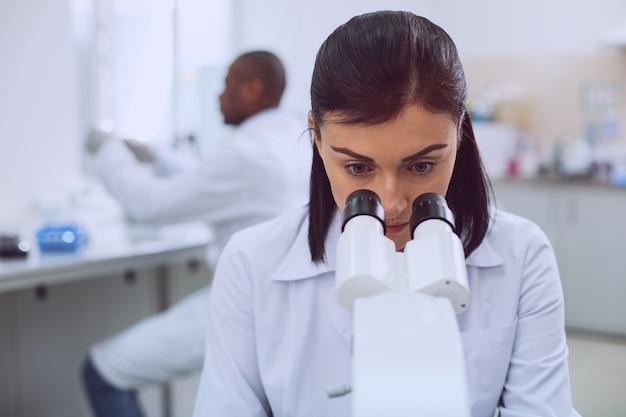 Kobiety w nauce. inteligentna, zdeterminowana badaczka pracująca nad swoim mikroskopem podczas pracy w laboratorium