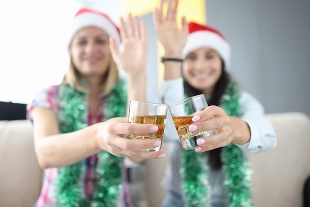 Kobiety w noworocznych dekoracjach iw czapkach mikołaja trzymają w rękach kieliszki z alkoholem i machają