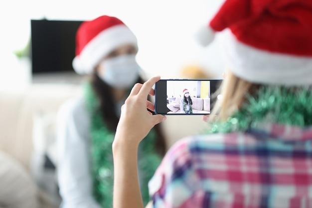 Kobiety w ochronnych maskach medycznych i czapkach świętego mikołaja fotografujące na zbliżeniu telefonu komórkowego