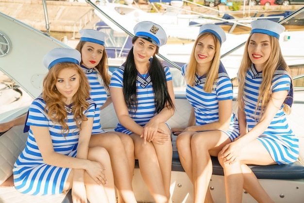 Kobiety w pasiastych sukienkach i czapkach, na pokładzie jachtu,