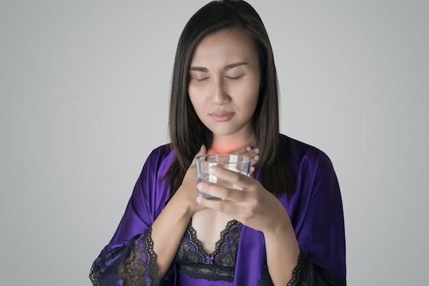 Kobiety w purpurowej jedwabnej koszuli nocnej i purpurowej szacie trzymającej szklankę wody mają ból gardła z powodu suchego gardła w nocy