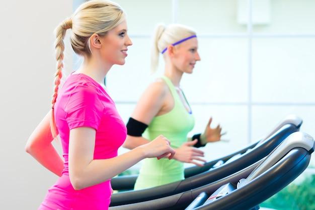 Kobiety w siłowni uprawiające sport na bieżni