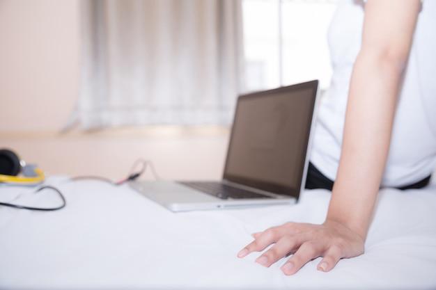 Kobiety w sportowej piżamie siedzą lub rozmawiają online z przyjaciółmi lub robią zakupy online. i zrelaksuj się w łóżku na wakacjach.