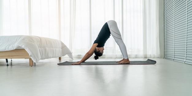 Kobiety w średnim wieku uprawiają jogę rano w sypialni,