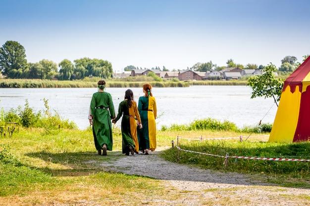 Kobiety w strojach średniowiecznych idą szlakiem nad rzekę