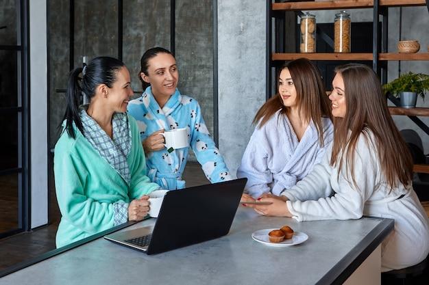 Kobiety w szlafrokach jedzą śniadanie przy stole w jadalni i rozmawiają, przeglądając wiadomości na laptopach