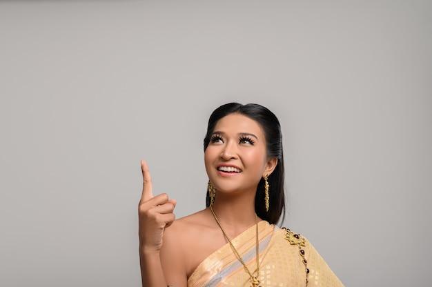 Kobiety w tajskich strojach symbolicznych, wskazujących palcami