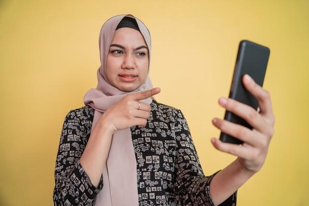 Kobiety w zasłonie czują się zniesmaczone, gdy patrzą na ekran telefonu z gestem wskazującym na s...