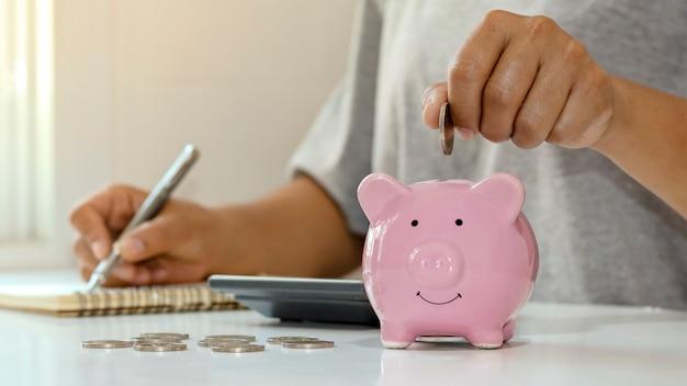 Kobiety wkładają srebrne monety do prosiąt, aby zaoszczędzić pieniądze i zaoszczędzić pieniądze na przyszłą inwestycję. koncepcja finansowa.