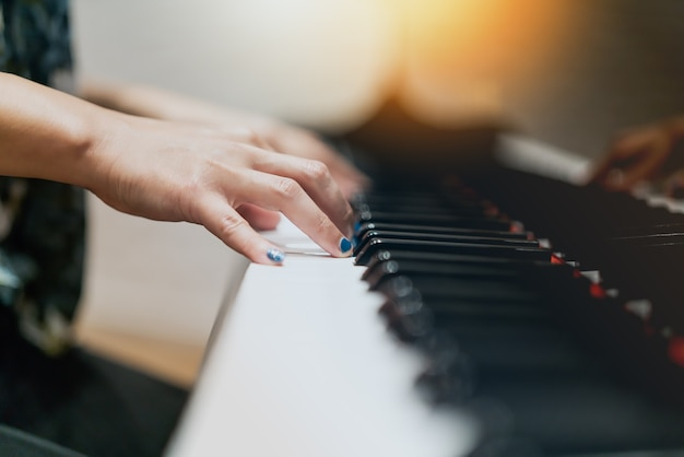 Kobiety wręczają na klasycznym fortepianowym klawiaturowym zbliżeniu