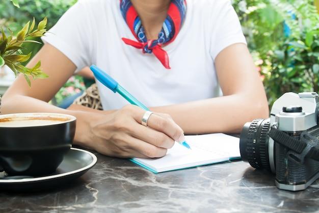Kobiety writing na dzienniczku z kawą i kamerą na stole