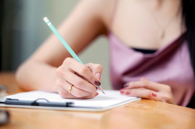Kobiety writing podczas gdy siedzący przy drewnianym stołem