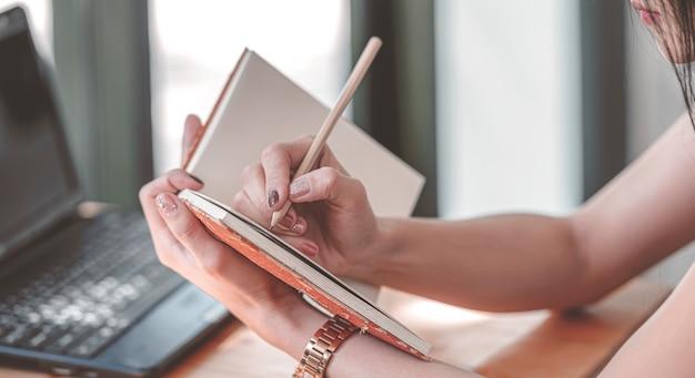 Kobiety writing w notatniku podczas gdy siedzący przy biurem