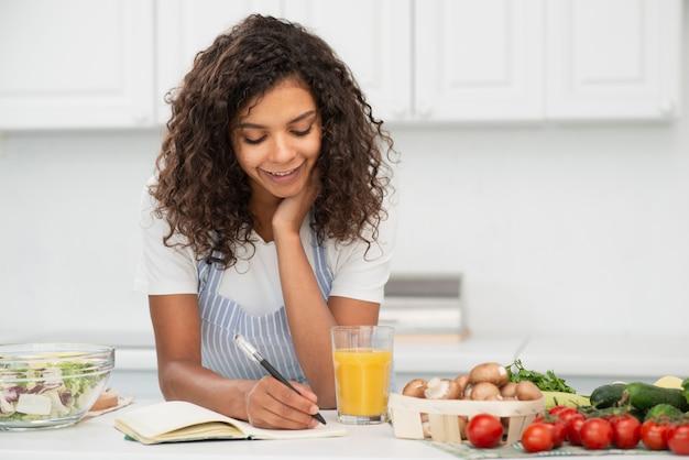 Kobiety writing w notatniku w kuchni