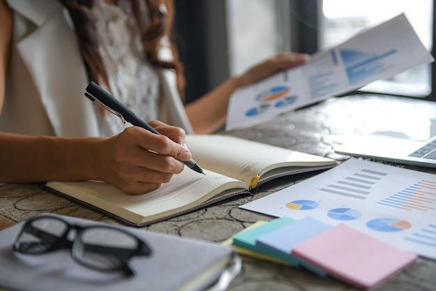 Kobiety wykonawcze sprawdzają dane z wykresów i robią notatki.