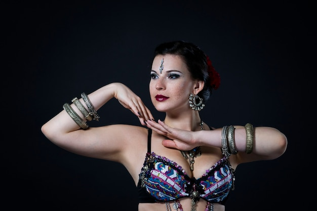 Kobiety wykonują taniec brzucha w etnicznej sukni na czarnym tle, wyśmienity