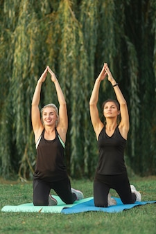 Kobiety wykonujące ćwiczenia jogi na zewnątrz