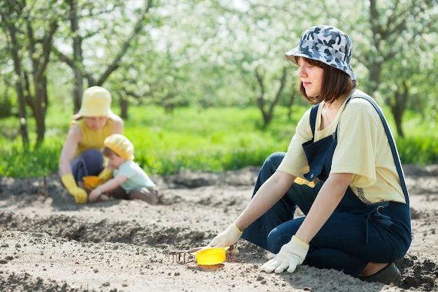 Kobiety z dzieckiem pracują w ogrodzie warzywnym