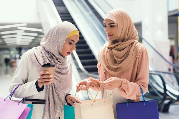 Kobiety z filiżanką kawy stojącą w centrum handlowym