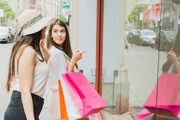 Kobiety z kolorowymi torba na zakupy blisko sklepowego okno