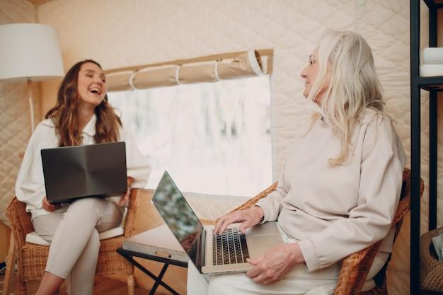 Kobiety z laptopem relaksując się w glampingowym namiocie kempingowym nowoczesnej koncepcji stylu życia wakacyjnego