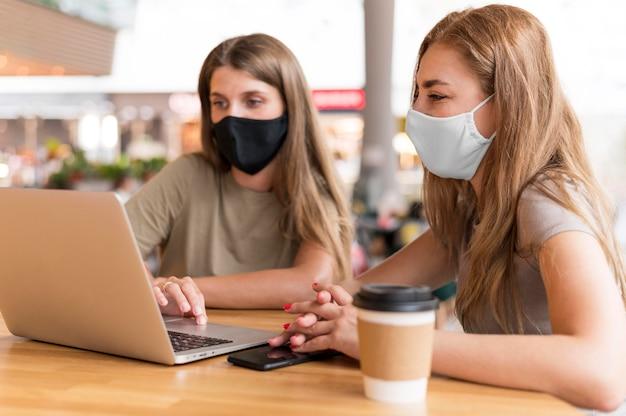 Kobiety z maską pracuje na laptopie