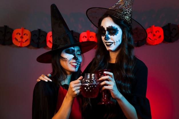 Kobiety z napojami przebranymi za czarownice