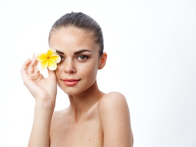 Kobiety z odkrytymi ramionami i zamkniętymi oczami trzymające kwiat i