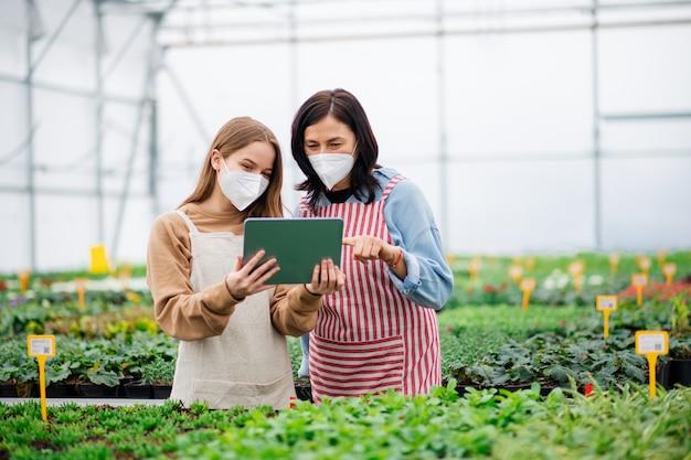Kobiety z tabletem pracujące w szklarni w centrum ogrodniczym, koncepcja koronawirusa.