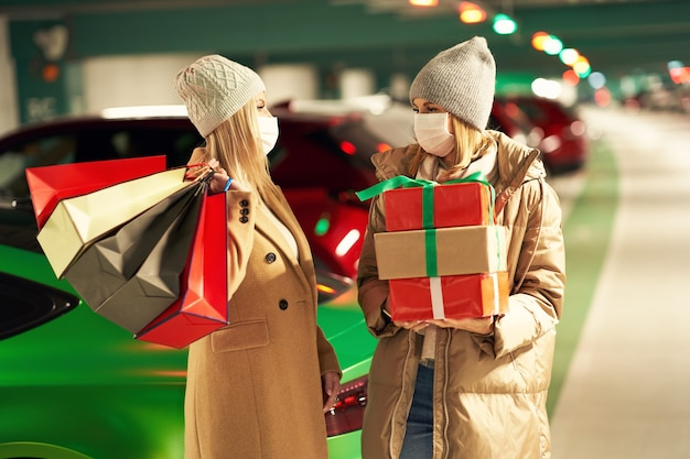 Kobiety z torbami na zakupy i świątecznymi prezentami w maskach na podziemnym parkingu