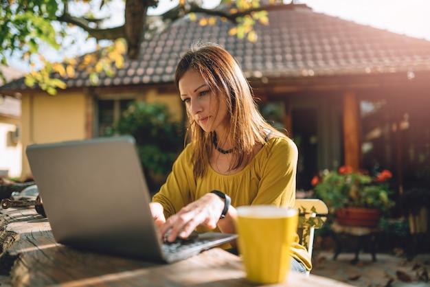 Kobiety za pomocą laptopa na podwórku patio