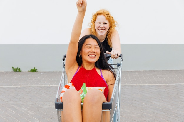 Kobiety zabawy z wózkiem na zakupy i patrząc na kamery