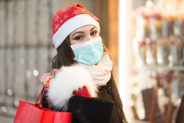 Kobiety zakupy na boże narodzenia podczas gdy będący ubranym maskę, coronavirus pandemiczny pojęcie