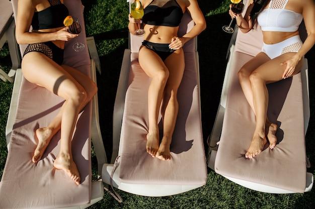 Kobiety ze świeżymi koktajlami wypoczywają na leżakach przy basenie w ośrodku. piękne dziewczyny relaksują się przy basenie w słoneczny dzień, letnie wakacje atrakcyjnych dziewczyn