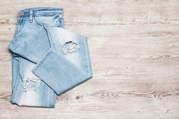 Kobiety zgrywanie obcisłe niebieskie dżinsy fashion style minimalne tło wolne miejsce na tekst