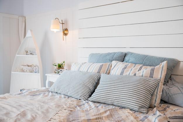 Koc na łóżko king size i kaktusy w złotych doniczkach na szafce w przestronnej sypialni. łóżko king size z miękką wezgłowiem i pastelową różową pościelą. pastelowy koc na łóżku w sypialni wnętrza