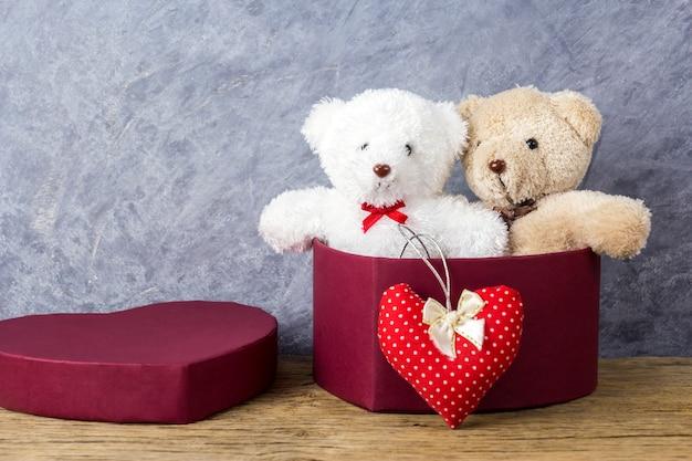Kocha pojęcia miś w czerwonym sercu prezenta pudełku na drewno stole dla valentines dnia