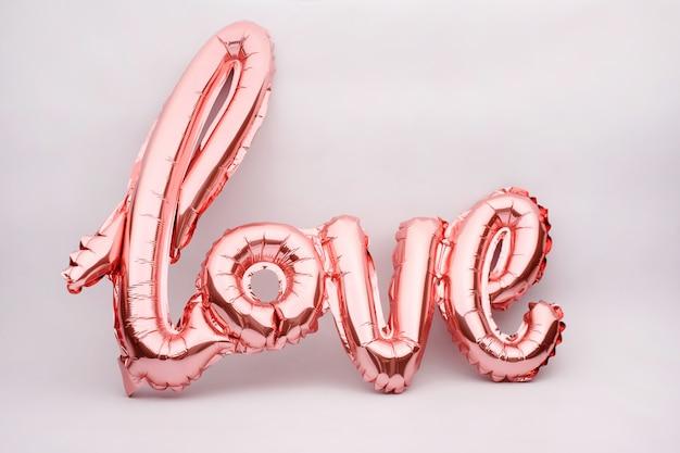 Kocha słowo od różowego nadmuchiwanego balonu na bielu