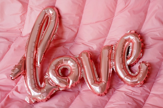 Kocha słowo od różowego nadmuchiwanego balonu na różowym tle. pojęcie romansu, walentynki. uwielbiam balon z różowego złota