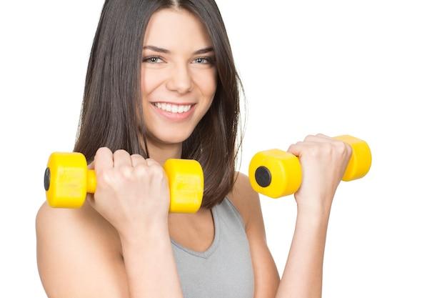 Kocha sport. zbliżenie portret zdrowej, uśmiechnięta młoda kobieta trzymając hantle lato na boku