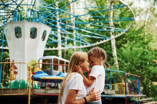 Kochać się nawzajem. wesoła dziewczynka jej mama dobrze się bawi w parku w pobliżu atrakcji.