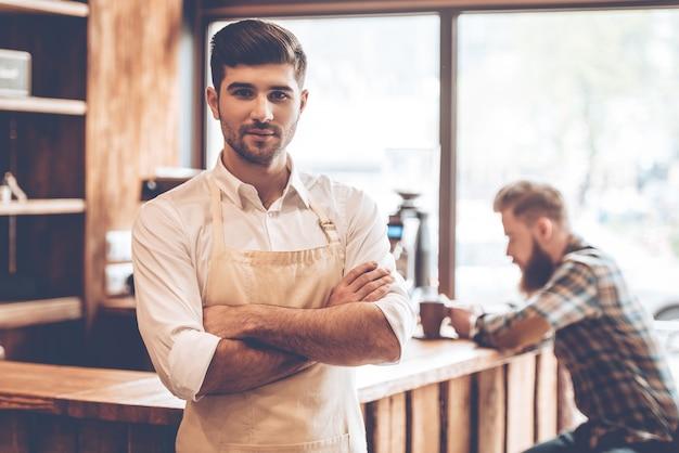 Kochać swoją pracę. młody przystojny mężczyzna w fartuchu, patrząc na kamerę i trzymając skrzyżowane ręce, stojąc w kawiarni z klientem w tle