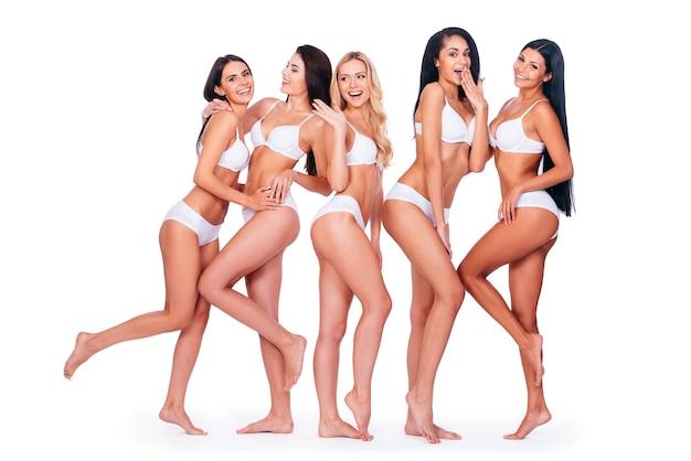 Kochać swoje ciała. pełna długość pięciu pięknych kobiet w bieliźnie pozujących i wyglądających naturalnie, stojąc razem na białym tle