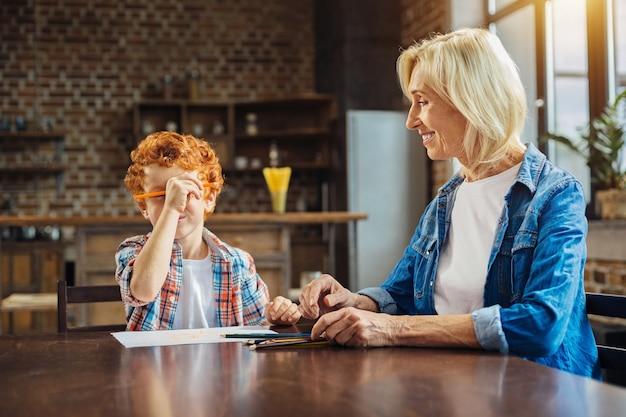 Kochaj go do księżyca iz powrotem. starsza pani siedząca obok swojego rudowłosego małego wnuka i patrząc na niego z uśmiechem na twarzy, podczas gdy on rysuje ołówkiem i żartuje.
