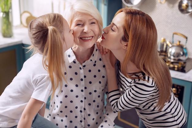 Kochaj naszą babcię. śliczna mała dziewczynka i jej matka całują starszą kobietę w policzki razem, podczas gdy kobieta uśmiecha się radośnie