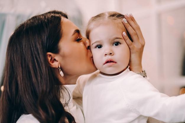Kochająca brunetka matka trzyma swoją małą uroczą córeczkę na ramionach i całuje ją w policzek