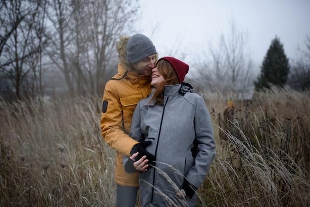Kochająca ciężarna para spaceruje poza miastem późną jesienią.