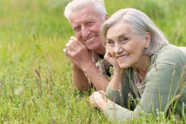 Kochająca dojrzała para leżąca na trawie w letnim parku